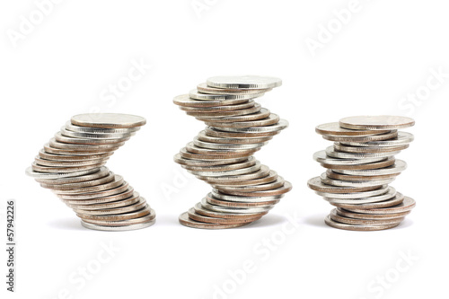 Curvilinear laid stacks of coins on white background