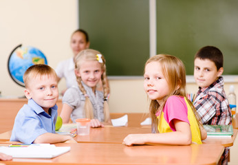 Portrait of schoolkids at workplace with teacher on background