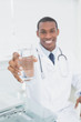 Male doctor holding out a glass of water in medical office