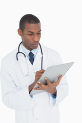 Serious male doctor writing on clipboard