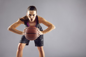 Beautiful woman in sportswear playing basketball