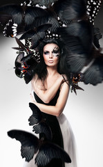 Woman with black hair and art make up and butterflies
