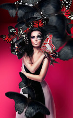Woman with black hair and art make up and  red butterflies