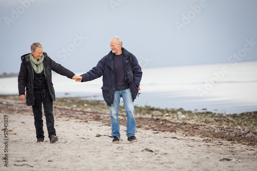 canvas print picture älteres glückliches paar macht einen strand spaziergang