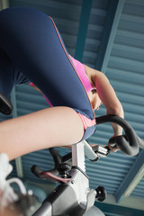 Determined young woman working out at spinning class