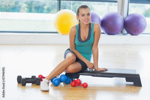 Young woman sitting with dumbbells in fitness studio