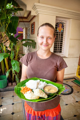 Woman with thali on banana leaf