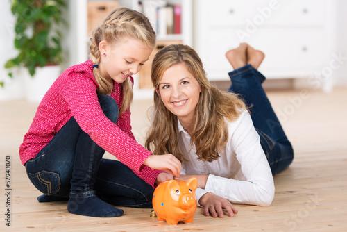 mutter und tochter füttern das sparschwein