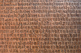 Background with ancient sanskrit text etched into a stone tablet poster