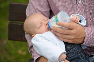 Vater gibt Säugling die Flasche