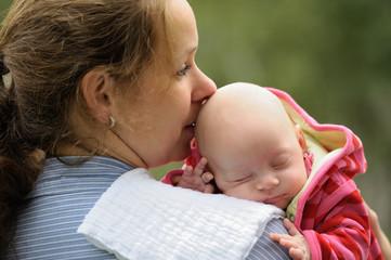 Glückliche Mutter hält ihr Baby auf dem Arm