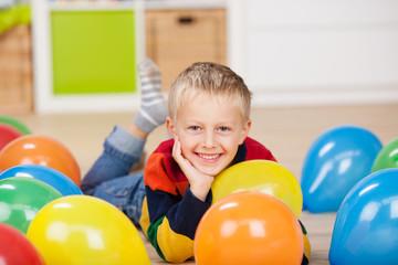 süßer kleiner junge liegt zwischen luftballons