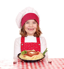 happy little girl cook with spaghetti on table