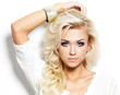 Beautiful blond woman with long curly hair and style makeup.