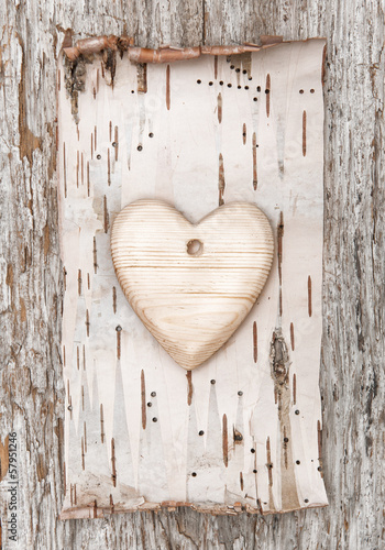 Wooden heart with birch bark on the old wood