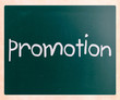 "The word ""promotion"" handwritten with white chalk on a blackboar"
