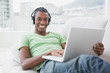Portrait of smiling Afro man with headphones using laptop on sof