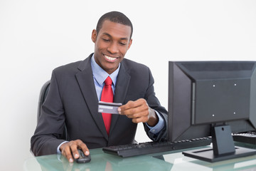 Smiling young Afro businessman doing online shopping