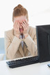 Worried businesswoman covering face at office