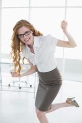 Elegant businesswoman cheering in office