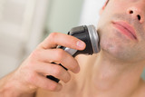 Extreme Close up of man shaving with electric razor