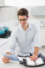 Casual man with digital tablet and diary in kitchen
