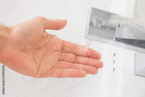 Hand under running water at bathroom sink