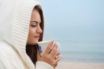 a young woman is drinking hot tea on the sea shore
