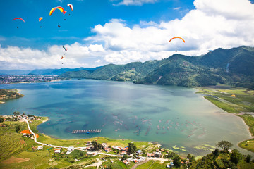 Paraglider flying over the  Fewa lake in Pokhara, Nepal.
