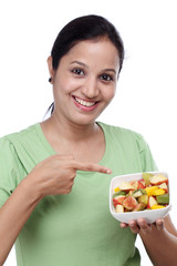 Young Indian woman showing fruit salad