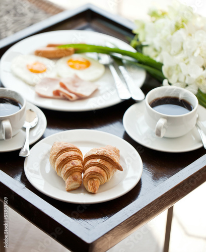 breakfast with cup of black coffee, eggs and croissants on balco