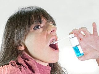 woman with  spray dispenser for sore throat