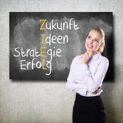 junge Frau vor Tafel mit ZIEL-Kreuzwort