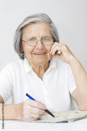 Senior woman solving crossword puzzle