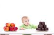 Kleiner Bub hat die Wahl zwischen Obst und Süssigkeiten