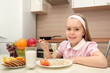 Cheerful little girl eats in the kitchen
