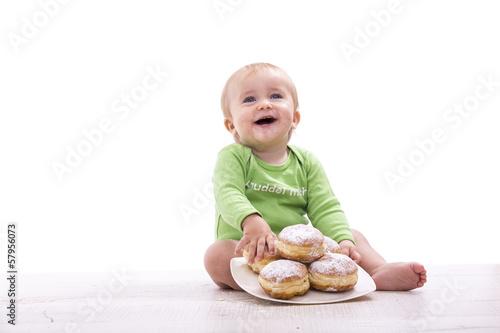 Kind freut sich über einen Teller mit Krapfen - 57956073