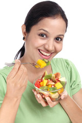 Young Indian woman eating fruit salad against white