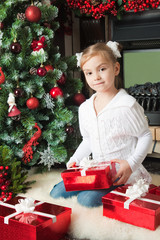 Girl in white jacket with gifts near christmas tree
