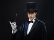 magician in top hat with magic wand showing trick