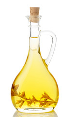 Olive oil with herbs in glass jug isolated on white background