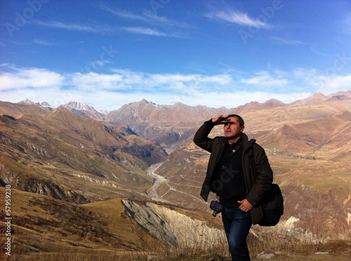 traveler in the mountains with a camera looking into distance