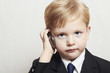 Little boy in business suit with cell phone.fashionable child