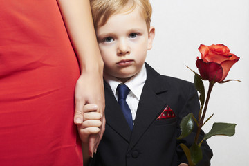 child in suit with mother. flower. red dress. family.little boy