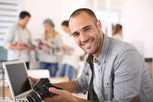 CHeerful reporter working in office on laptop - 57959472