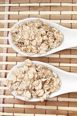 wheat flakes on white ceramic spoon