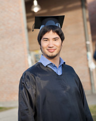 Male Student In Graduation Gown And Mortar Board On Campus