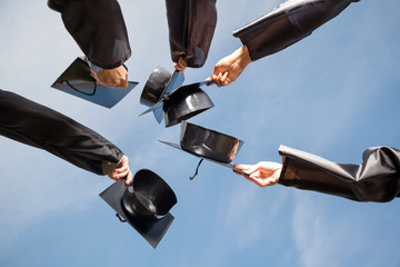 Students Raising Mortar Boards Against Sky On Graduation Day