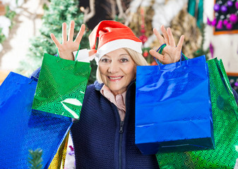 Woman With Shopping Bags Standing At Christmas Store