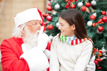 Santa Claus Gesturing Finger On Lips At Girl